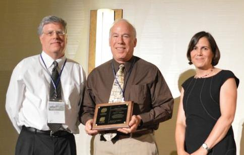 Philip Singer of the University of North Carolina, Chapel Hill accepts the Charles R. O'Melia Distinguished Educator Award from incoming president Jennifer Becker and awards committee chair Chad Jafvert